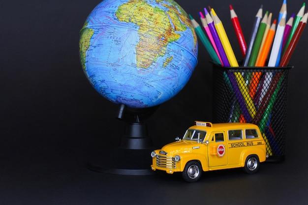 Концепция образования и возвращения в школу. канцелярские товары в стакане, глобус и желтый игрушечный автомобиль школьный автобус на столе на черном фоне