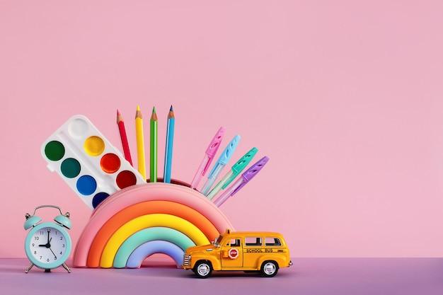Концепция образования и возвращения в школу. канцелярские товары в пенале, будильник и игрушечный автомобиль школьный автобус на столе на розовом фоне
