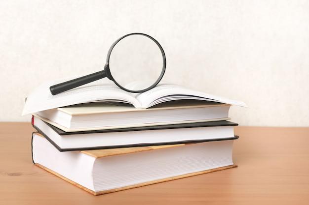教育の概念、情報と知識の検索。本の山の上の虫眼鏡