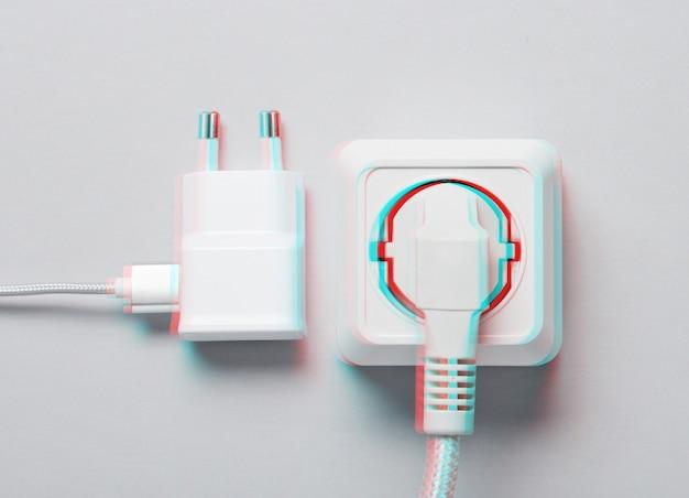 전기 의존의 개념. 플러그는 회색 배경에 전원 콘센트와 충전기에 연결되어 있습니다. 글리치 효과. 평면도