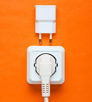 전기 의존의 개념. 플러그가 전원 콘센트와 주황색 배경의 충전기에 연결되었습니다. 평면도