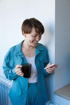 고용, 인터뷰, 광고 디지털 기술의 개념-커피를 마시고 전화로 이야기하는 여성. 컵 웃는 여자를 호출합니다. 여자의 아침