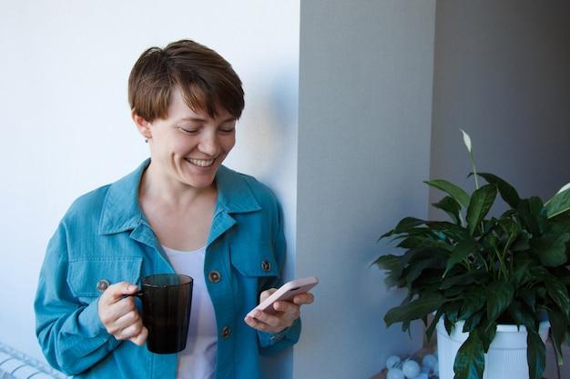 고용, 인터뷰, 광고 디지털 기술의 개념-커피를 마시고 전화로 이야기하는 여성. 컵 웃는 여자를 호출합니다.