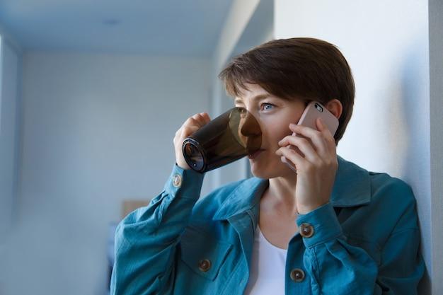 고용, 인터뷰, 광고 디지털 기술의 개념-커피를 마시고 전화로 이야기하는 여성