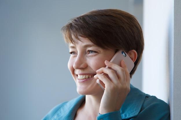 雇用、面接、広告デジタル技術の概念-電話で話している女性。笑顔の女性が電話をかけます。白い背景で隔離。コピースペース