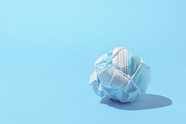 パンデミックを終わらせるという概念。しわくちゃの医療用マスク。