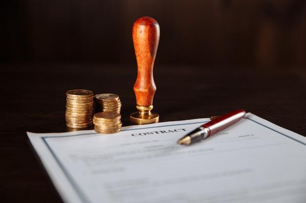 金融とビジネスの概念。木製のテーブルに契約書、切手、お金、ペン。