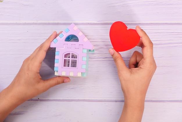 金融の概念、家と赤い心を手に持つ概念