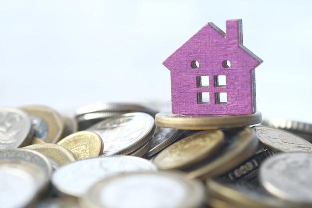 コインのスタックとテーブルの上の家と金融の概念の概念