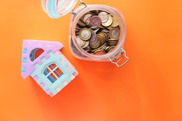Концепция финансовой концепции со стопкой монет и домом