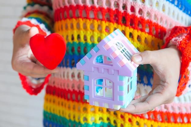 金融の概念、家と赤い心を手に持っている女性の概念