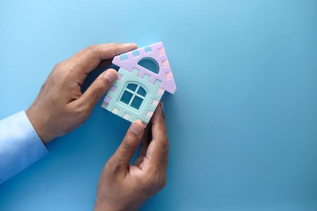 金融の概念の概念、手に家を持っている若い男。