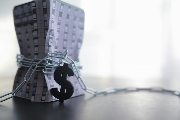 借り入れた資金への財政的依存の概念。住宅ローンの借金。家はドル記号の付いた巻尺で引っ張られます。