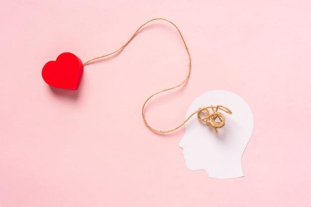 Концепция поиска любви белый бумажный силуэт головы с запутанными нитками внутри