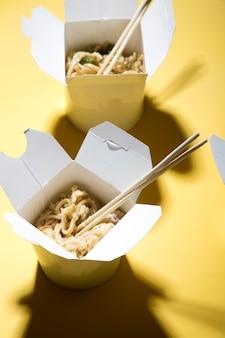 Концепция доставки еды на желтом фоне лапша в коробках