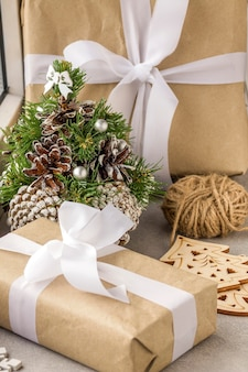 クリスマスと新年の贈り物の概念。窓際の装飾的なクリスマスツリーの近くにリボン付きの紙のギフトボックス。