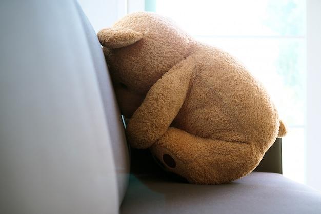 Концепция горя детей. плюшевый мишка сидит на диване в доме, один выглядит грустным и разочарованным.
