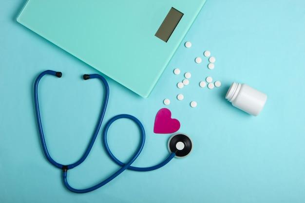 Концепция здорового похудения. стетоскоп, весы, бутылка таблеток на синем фоне. вид сверху