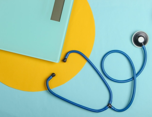 Концепция здорового похудения. стетоскоп, весы на сине-желтом фоне. вид сверху