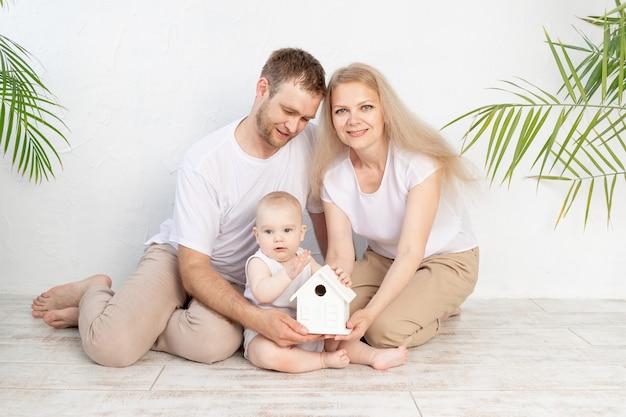 若い家族のための住宅や住宅ローンの概念。母父と赤ちゃんは家のモックアップを保持します