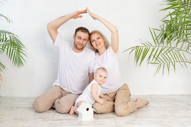 젊은 가족을위한 주택 또는 모기지 개념. 어머니와 아버지는 아기를 품에 안고 손으로 지붕을 만들었습니다.