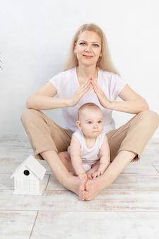 젊은 가족을위한 주택 또는 모기지 개념. 어머니는 아기를 팔에 안고 손으로 지붕을 만들었습니다.