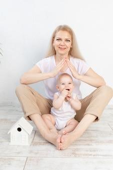 젊은 가족을 위한 주택이나 모기지 개념. 엄마는 아기를 팔에 안고 손으로 지붕을 만들었습니다.