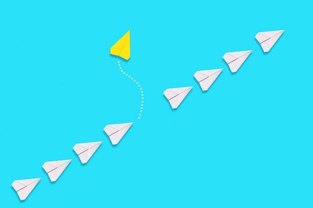 독립성과 개성의 개념. 노란색 종이 비행기가 흰색 비행기의 대기열에서 날아갑니다. 파란색 배경입니다. 플랫 레이.