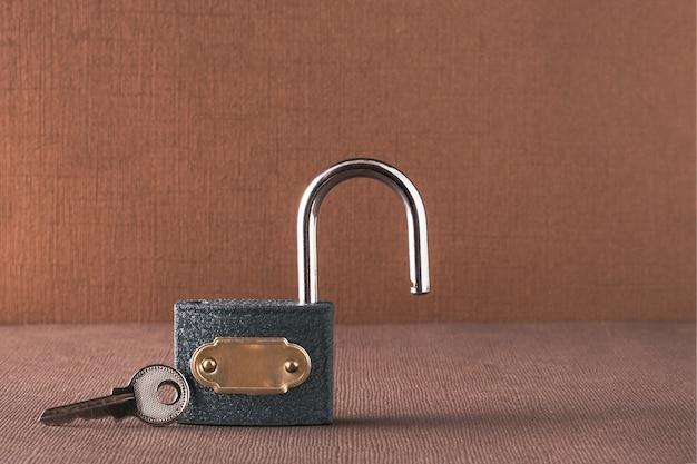 Понятие информационной безопасности. на светло-коричневом фоне открытый замок с лежащим рядом ключом.