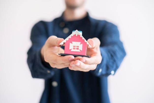 保険資産の概念、小さな家のおもちゃを持って、不動産を保護する手