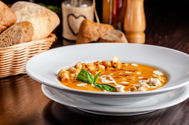 이탈리아 요리의 개념. 오렌지 맛, 닭고기 조각, 빵 크루통 및 크림 호박 크림 수프. 테이블에 레드 와인의 문자열. 레스토랑에서 요리 제공