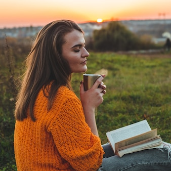 秋のライフスタイルと家族向けアウトドアレクリエーションのコンセプト。女性はサーモカップで格子縞の本を読みます。秋。日没。居心地の良い