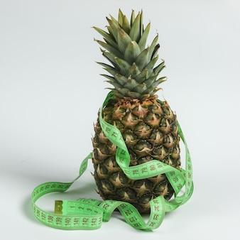 Концепция похудения. фруктовая диета. ананас, завернутый в измерительную ленту на белом фоне