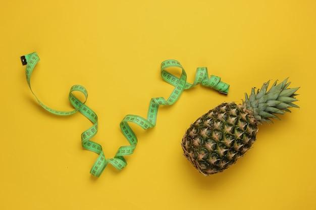 Концепция похудения. ананас, обернутый измерительной лентой на желтом фоне. здоровое питание. вид сверху