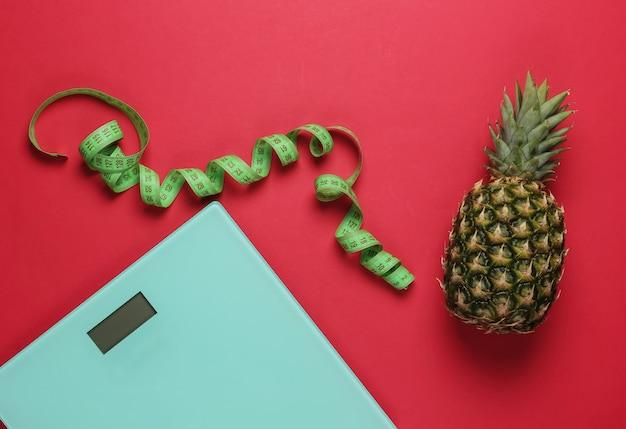 Концепция похудения. весы, ананас с измерительной лентой на красном фоне. здоровое питание. вид сверху