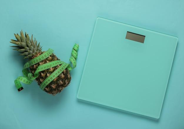 Концепция похудения. весы, ананас, обернутый измерительной лентой на синем пастельном фоне. здоровое питание. вид сверху