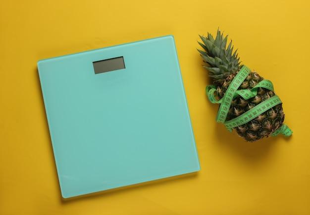 Концепция похудения. весы, ананас, обернутый измерительной лентой на желтом фоне. здоровое питание. вид сверху