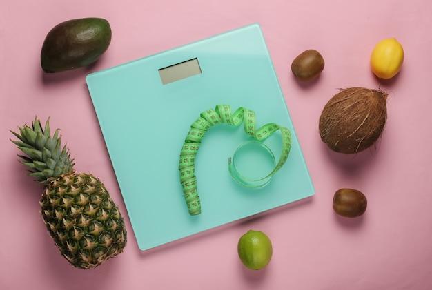 Концепция похудения. весы, линейка, тропические фрукты на розовом пастельном фоне. здоровое питание. вид сверху