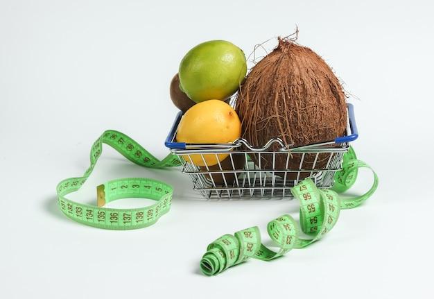Концепция похудения. тропические фрукты и измерительная лента в корзине для покупок на белом фоне. здоровое питание. фруктовая диета. вид сверху