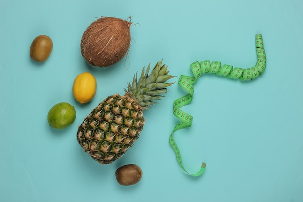 Концепция похудения. тропические фрукты и измерительная лента на синем фоне. здоровое питание. фруктовая диета. вид сверху