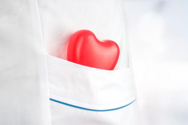 의학 및 건강 보험의 개념입니다. 의료 가운 주머니에 고무 심장. 건강 관리 및 환자, 실패 및 질병 개념. 매년 건강검진.