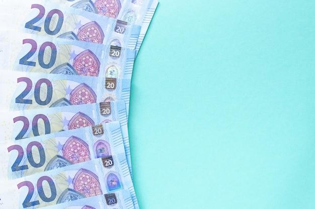 Понятие денег и финансов. банкноты номиналом 20 евро выложены на синем фоне с левой стороны. с местом для текста.