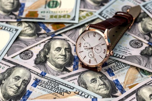 ハンドヘルド時計とドル紙幣のお金の概念