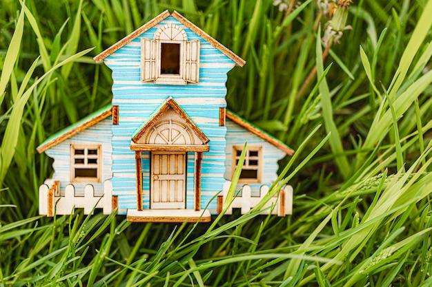 住宅ローンと賃貸住宅と不動産の概念。住宅ローンの信用貸付。緑の若い草の家のレイアウト。環境にやさしい住宅を購入する。自然の中で街の外の家。
