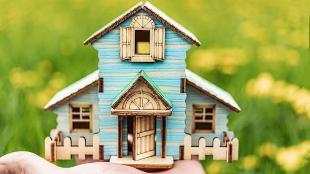 住宅ローンと賃貸住宅と不動産の概念。住宅ローンの信用貸付。緑の牧草地を背景に男の手に家のレイアウト。環境にやさしい住宅。