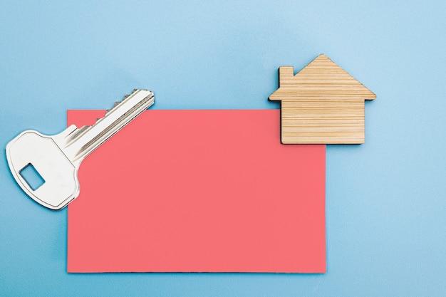 주택 및 부동산의 모기지, 판매 및 임대의 개념. 아파트 열쇠가 있는 명함과 목조 주택 모형. 공간을 복사합니다. 모형.