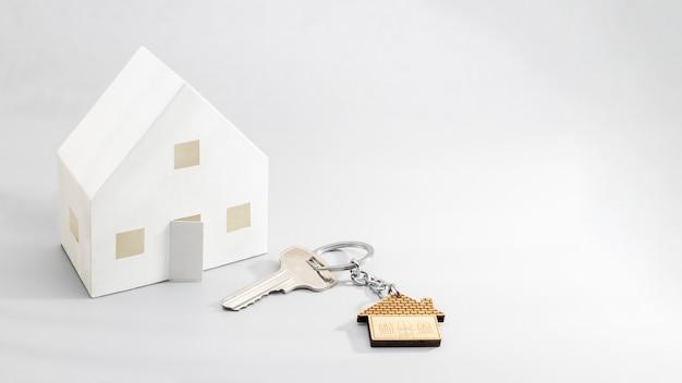 Понятие ипотеки, продажи и аренды жилья и недвижимости. ипотечное кредитование. макет бумажного домика с ключами и брелком в виде домика. формат баннера. скопируйте пространство.