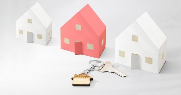 Понятие ипотеки, продажи и аренды жилья и недвижимости. ипотечное кредитование. макеты бумажных домиков с ключами и брелок в виде домика. формат баннера. скопируйте пространство.