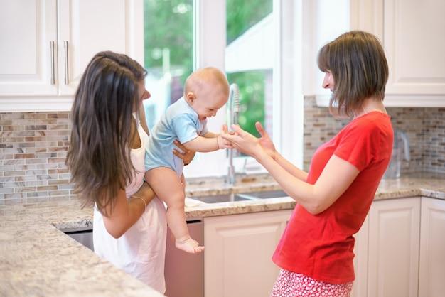 Понятие материнства, няни, младенчества и детства. две женщины и ребенок на руках.