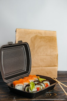 巻き寿司の非接触配送のコンセプト。別のロールと木製のテーブルのクラフトパッケージと黒のパッケージ。